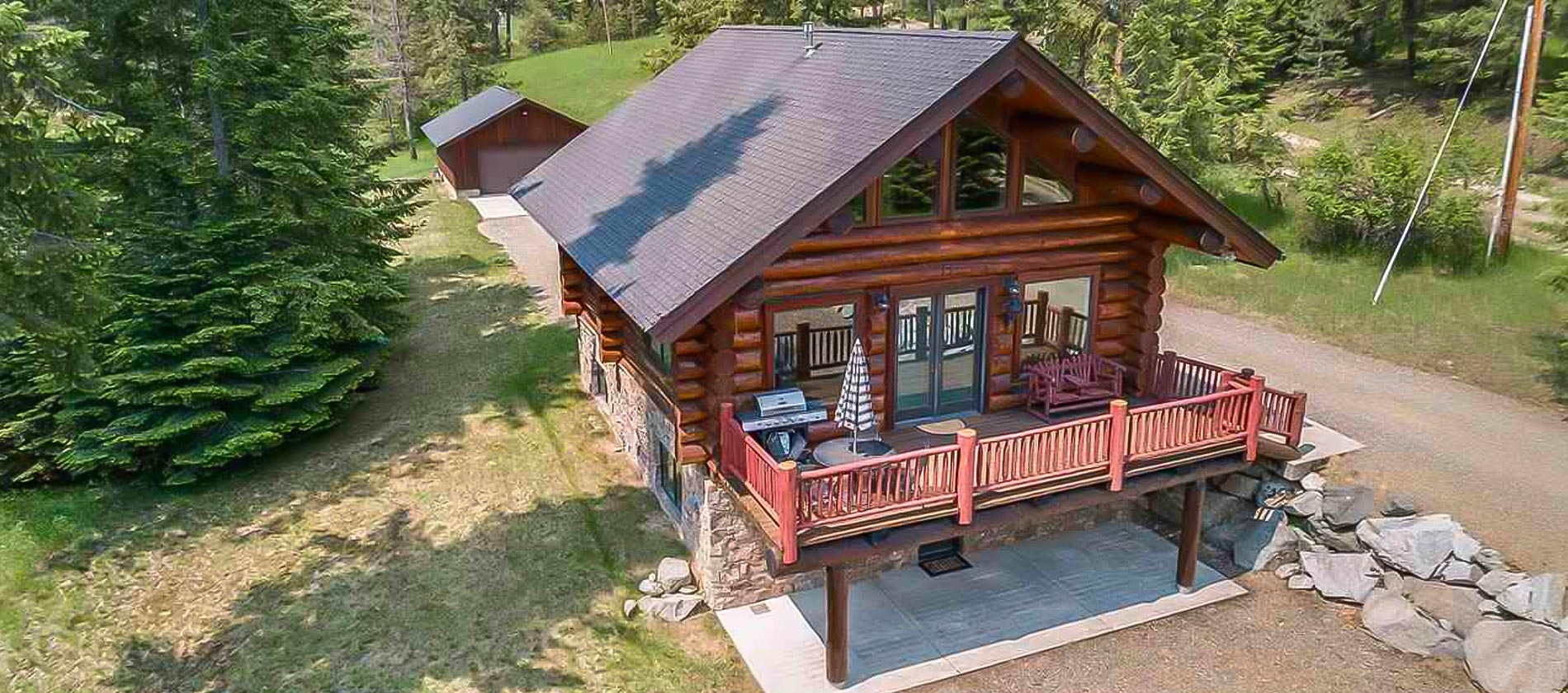 Beautiful custom log home with dry stack native rock, resting by a cedar adorned stream